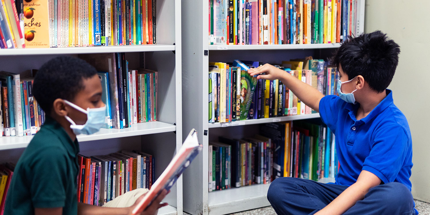 Students sitting in front of bookshelves reading.