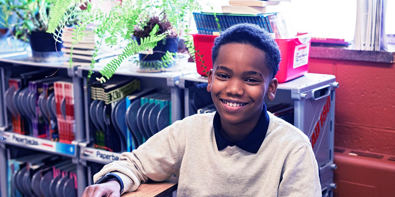 微笑着坐在桌旁的小学生.