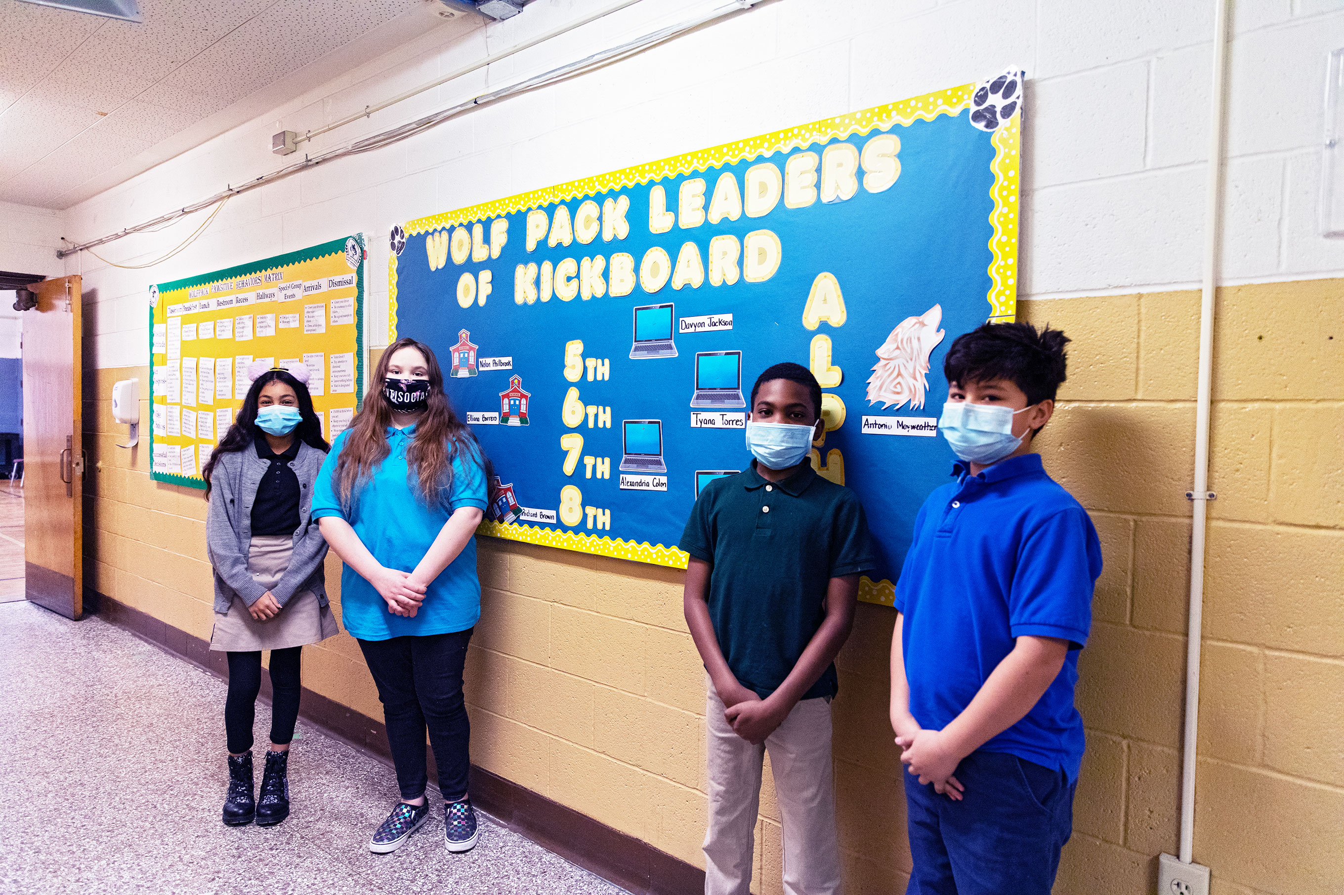 Students standing in hallway in front of Wolf Pack Leaders bulletin board.
